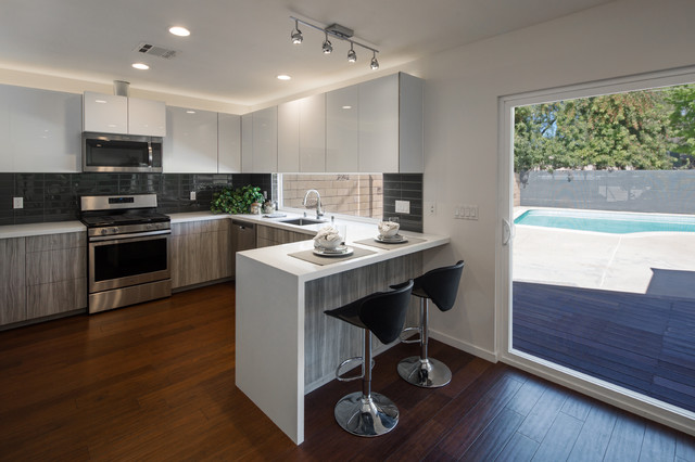 Mid-sized trendy l-shaped dark wood floor and brown floor eat-in kitchen photo in Los Angeles with an undermount sink, flat-panel cabinets, white cabinets, quartz countertops, gray backsplash, porcelain backsplash, stainless steel appliances and a peninsula