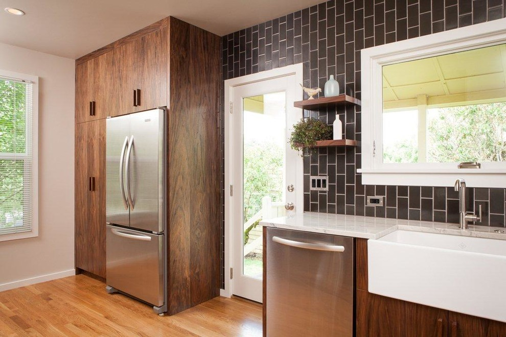 Enclosed kitchen - contemporary enclosed kitchen idea in Portland with a farmhouse sink, flat-panel cabinets, dark wood cabinets, quartzite countertops, black backsplash, ceramic backsplash and stainless steel appliances