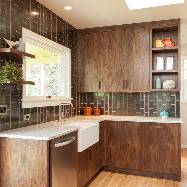 Inspiration for a mid-century modern light wood floor enclosed kitchen remodel in Portland with a farmhouse sink, flat-panel cabinets, dark wood cabinets, quartzite countertops, black backsplash, ceramic backsplash and stainless steel appliances