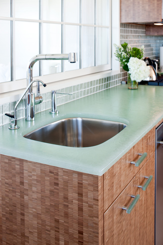 Small beach style l-shaped light wood floor eat-in kitchen photo in Boston with an undermount sink, flat-panel cabinets, light wood cabinets, glass countertops, green backsplash, stainless steel appliances, no island, glass tile backsplash and turquoise countertops