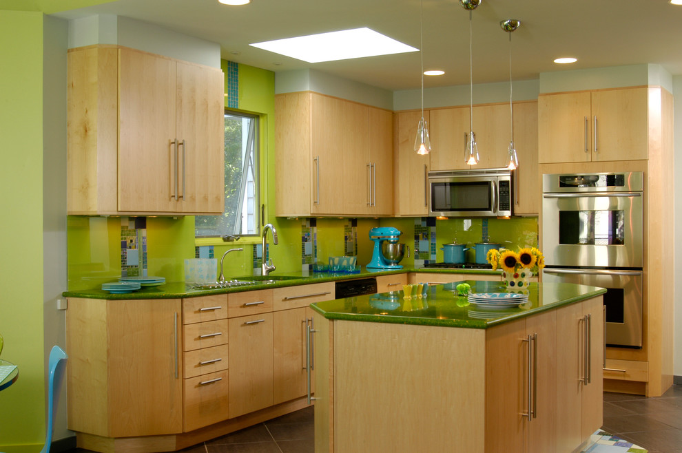 Inspiration for a mid-sized eclectic l-shaped ceramic tile eat-in kitchen remodel in New York with flat-panel cabinets, light wood cabinets, green backsplash, glass tile backsplash, stainless steel appliances, an undermount sink, quartz countertops and an island