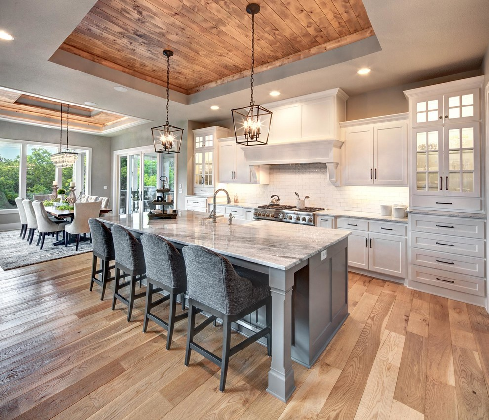 Example of a classic light wood floor and beige floor eat-in kitchen design in Kansas City with a farmhouse sink, glass-front cabinets, white cabinets, white backsplash, subway tile backsplash, stainless steel appliances, an island and gray countertops