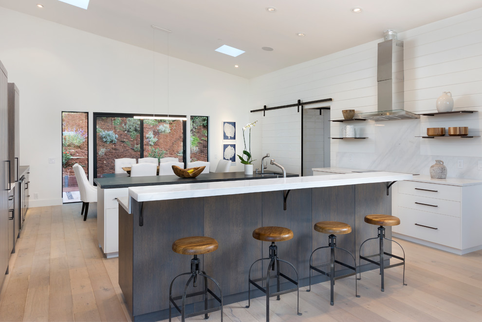 Inspiration for a mid-sized contemporary u-shaped light wood floor and beige floor eat-in kitchen remodel in San Francisco with flat-panel cabinets, white cabinets, two islands, white countertops, quartz countertops, white backsplash, wood backsplash and stainless steel appliances