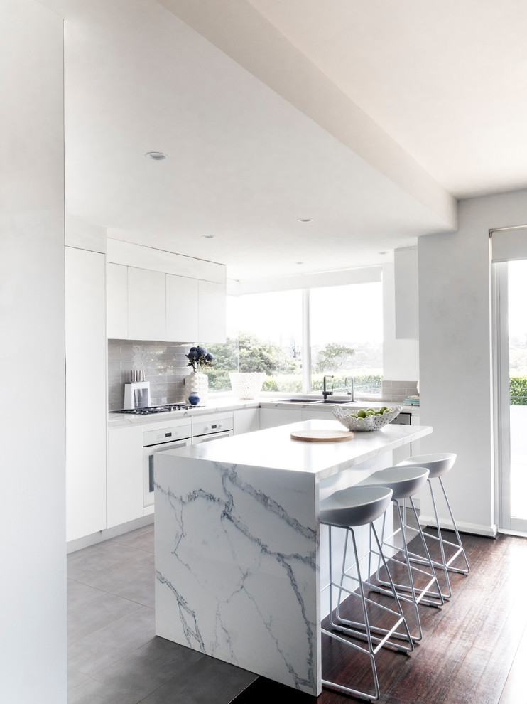 This is an example of a contemporary l-shaped kitchen in Sydney with an undermount sink, flat-panel cabinets, white cabinets, grey splashback, panelled appliances and white benchtop.
