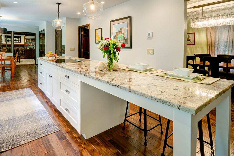 Example of a mid-sized transitional galley medium tone wood floor eat-in kitchen design in Columbus with an island, shaker cabinets, white cabinets, granite countertops, white backsplash, subway tile backsplash, stainless steel appliances and a double-bowl sink