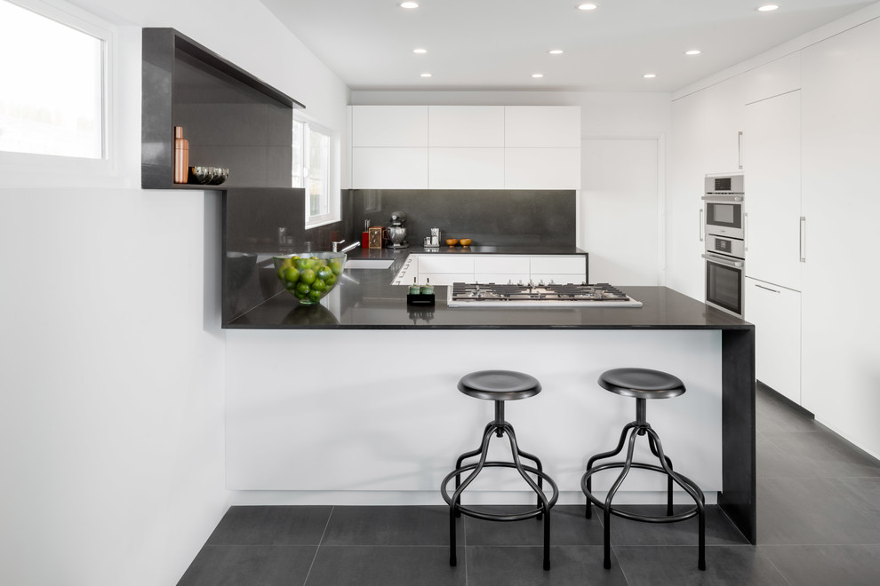 Inspiration for a contemporary u-shaped eat-in kitchen remodel in Los Angeles with flat-panel cabinets, white cabinets, paneled appliances, a peninsula, quartz countertops, black backsplash and an undermount sink