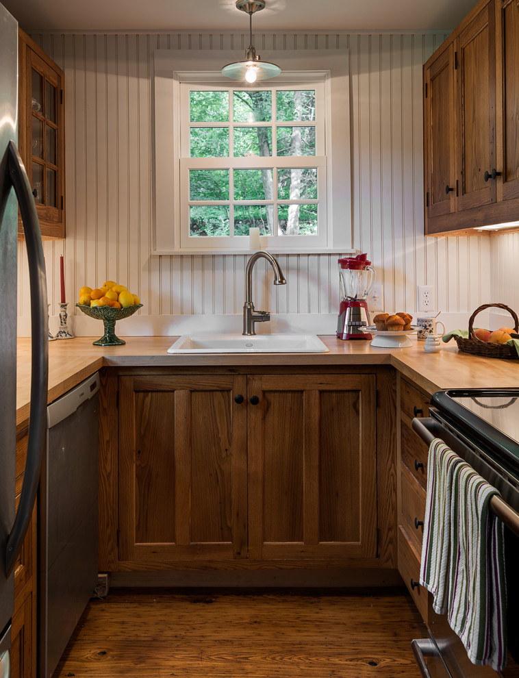 Inspiration for a small timeless u-shaped enclosed kitchen remodel in New York with a drop-in sink, recessed-panel cabinets, dark wood cabinets, wood countertops and stainless steel appliances