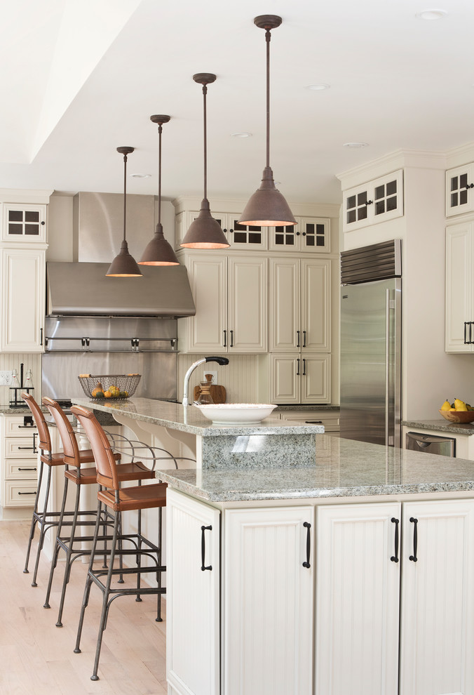Kitchen - large traditional beige floor kitchen idea in New York with raised-panel cabinets, beige cabinets, metallic backsplash, stainless steel appliances, an island, gray countertops, granite countertops and metal backsplash