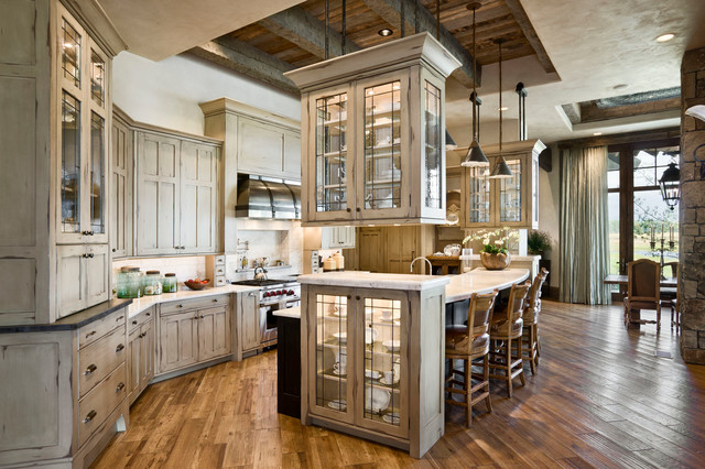 Eat-in kitchen - rustic eat-in kitchen idea in Other with glass-front cabinets, beige cabinets, beige backsplash and stainless steel appliances