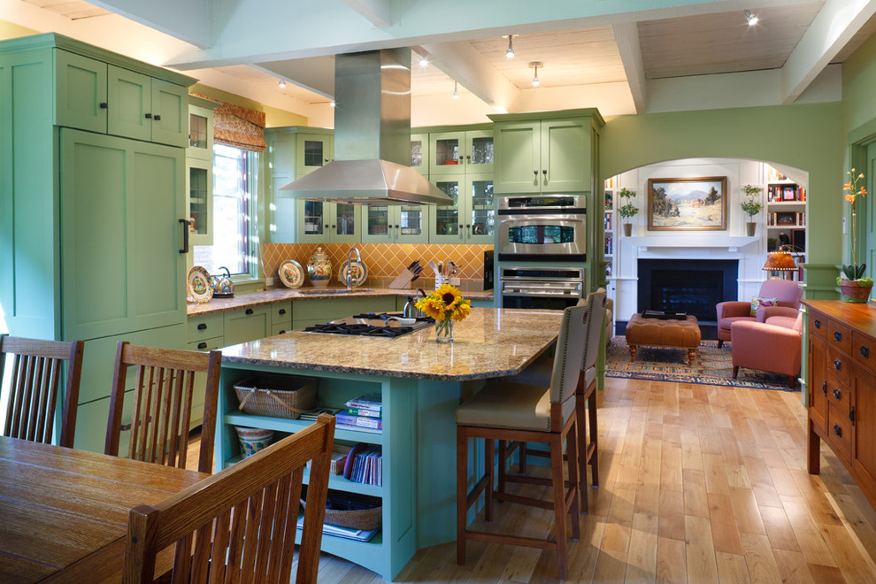 Inspiration for a mid-sized farmhouse l-shaped light wood floor and brown floor eat-in kitchen remodel in Boston with green cabinets, beige backsplash, paneled appliances, an undermount sink, shaker cabinets, granite countertops, ceramic backsplash and an island