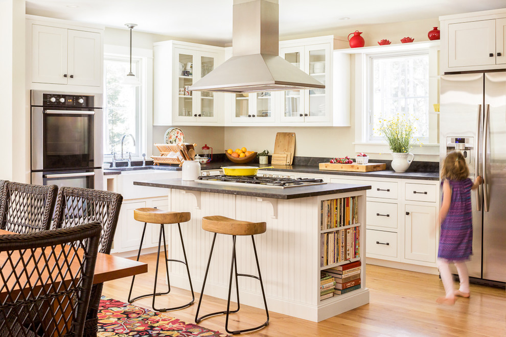 Inspiration for a mid-sized timeless l-shaped light wood floor and brown floor eat-in kitchen remodel in Portland Maine with a farmhouse sink, glass-front cabinets, white cabinets, stainless steel appliances, an island, granite countertops and window backsplash