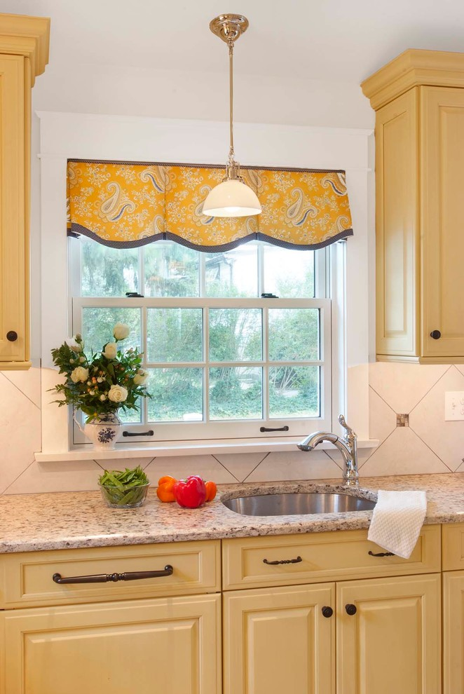 Mid-sized elegant porcelain tile eat-in kitchen photo in Philadelphia with an undermount sink, raised-panel cabinets, yellow cabinets, granite countertops, beige backsplash, porcelain backsplash, paneled appliances and an island