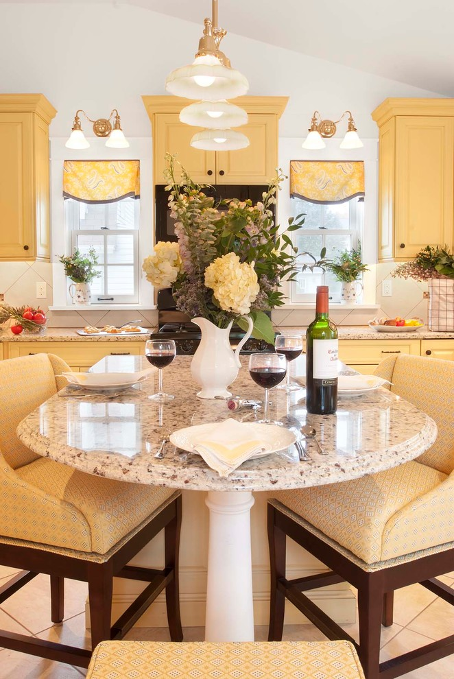 Example of a classic porcelain tile eat-in kitchen design in Philadelphia with an undermount sink, raised-panel cabinets, yellow cabinets, granite countertops, beige backsplash, porcelain backsplash, paneled appliances and an island