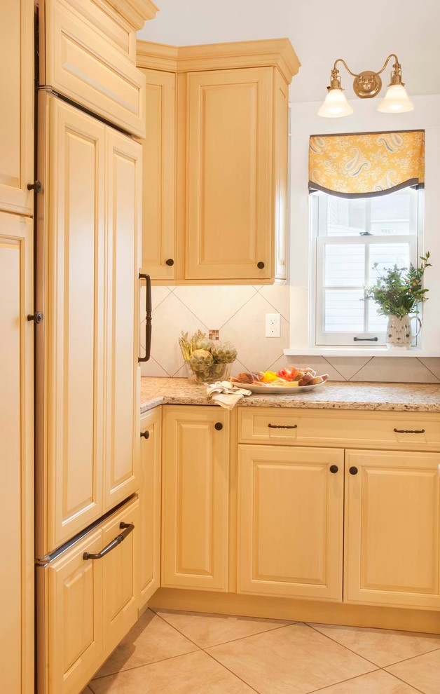 Inspiration for a mid-sized timeless porcelain tile eat-in kitchen remodel in Philadelphia with an undermount sink, raised-panel cabinets, yellow cabinets, granite countertops, beige backsplash, porcelain backsplash, paneled appliances and an island