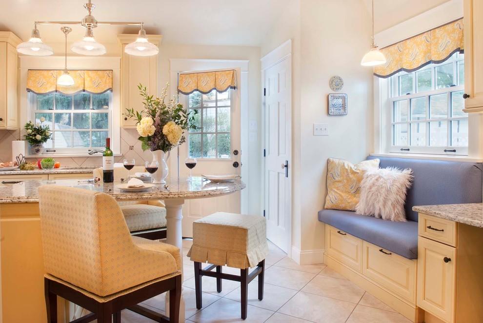 Mid-sized elegant u-shaped porcelain tile eat-in kitchen photo in Philadelphia with an undermount sink, raised-panel cabinets, yellow cabinets, granite countertops, beige backsplash, porcelain backsplash, paneled appliances and an island