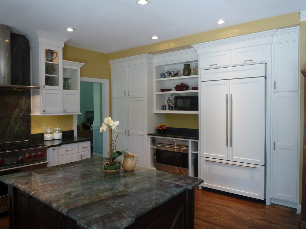 Mid-sized transitional l-shaped dark wood floor and brown floor eat-in kitchen photo in DC Metro with an undermount sink, shaker cabinets, white cabinets, solid surface countertops, multicolored backsplash, stone slab backsplash, stainless steel appliances, an island and black countertops