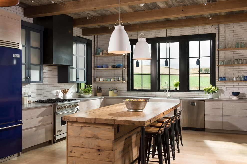 Example of a farmhouse l-shaped light wood floor and beige floor kitchen design in Other with a farmhouse sink, open cabinets, light wood cabinets, wood countertops, white backsplash, subway tile backsplash, colored appliances and an island