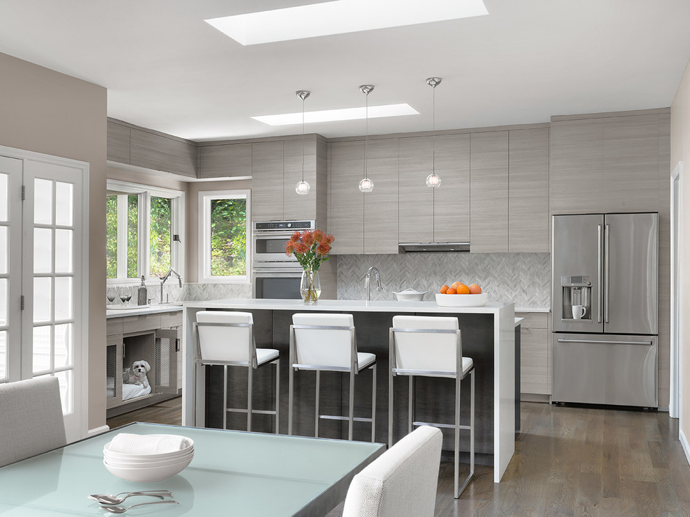 Example of a mid-sized trendy l-shaped medium tone wood floor and brown floor eat-in kitchen design in St Louis with flat-panel cabinets, gray cabinets, gray backsplash, stainless steel appliances, an island, white countertops, quartz countertops and porcelain backsplash