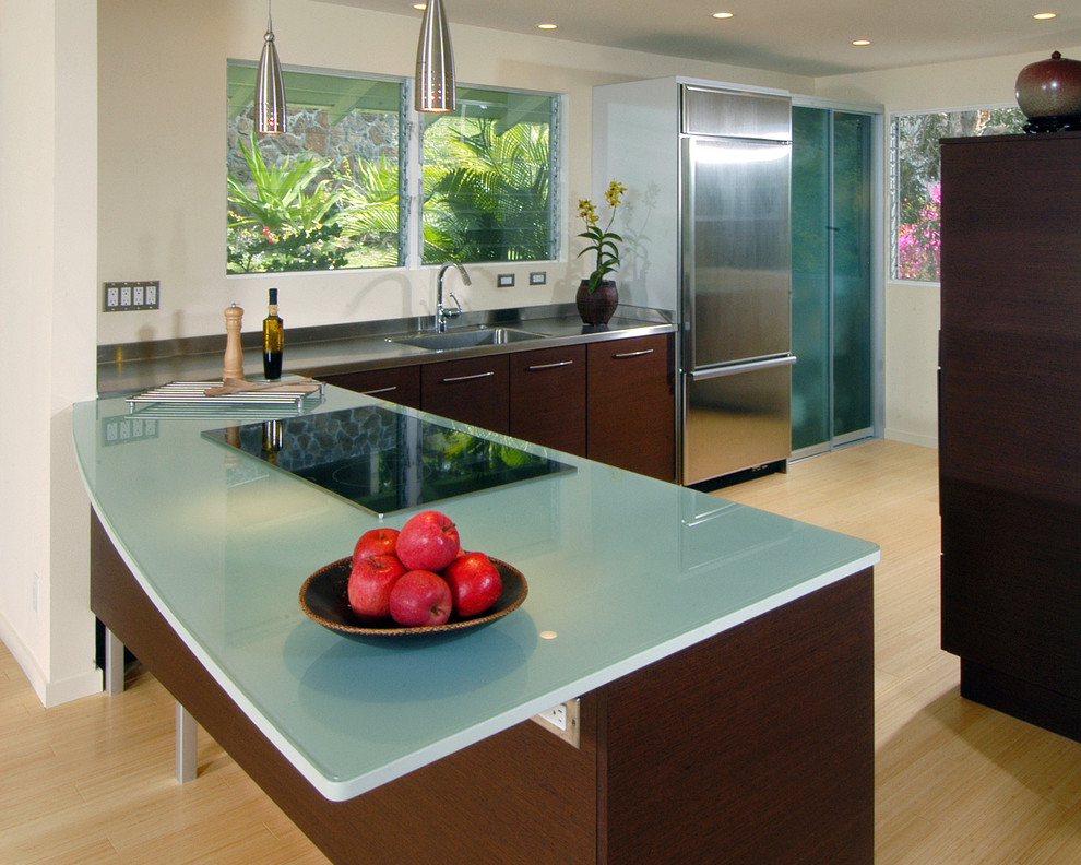 Kitchen - contemporary l-shaped kitchen idea in Hawaii with flat-panel cabinets, stainless steel appliances, an integrated sink, dark wood cabinets, glass countertops and turquoise countertops