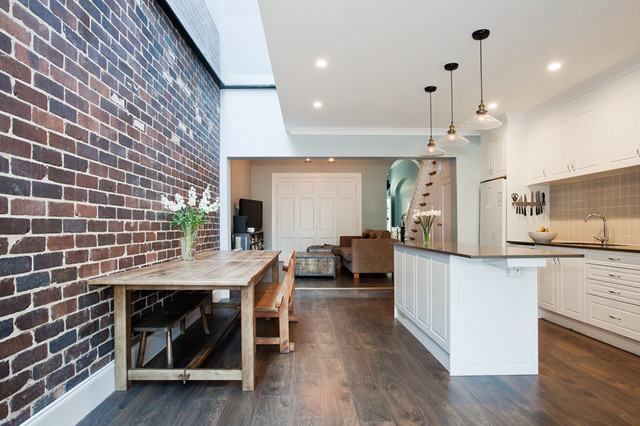 Example of a transitional dark wood floor kitchen design in Sydney with shaker cabinets, white cabinets, beige backsplash, white appliances and an island