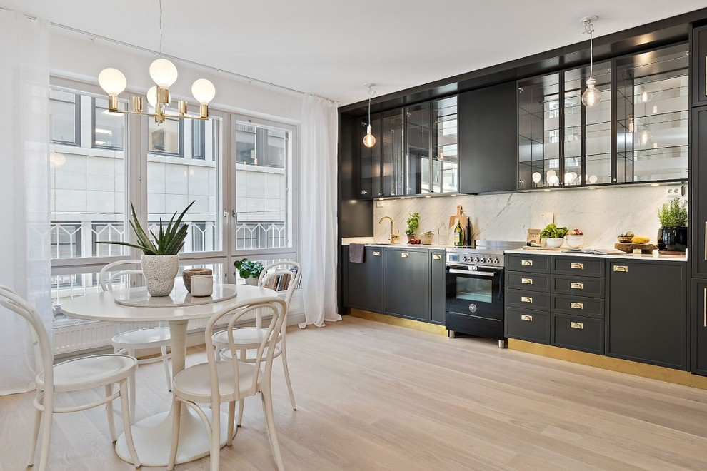 Example of a mid-sized danish single-wall light wood floor eat-in kitchen design in Stockholm with beaded inset cabinets, black cabinets, marble countertops, stainless steel appliances and no island