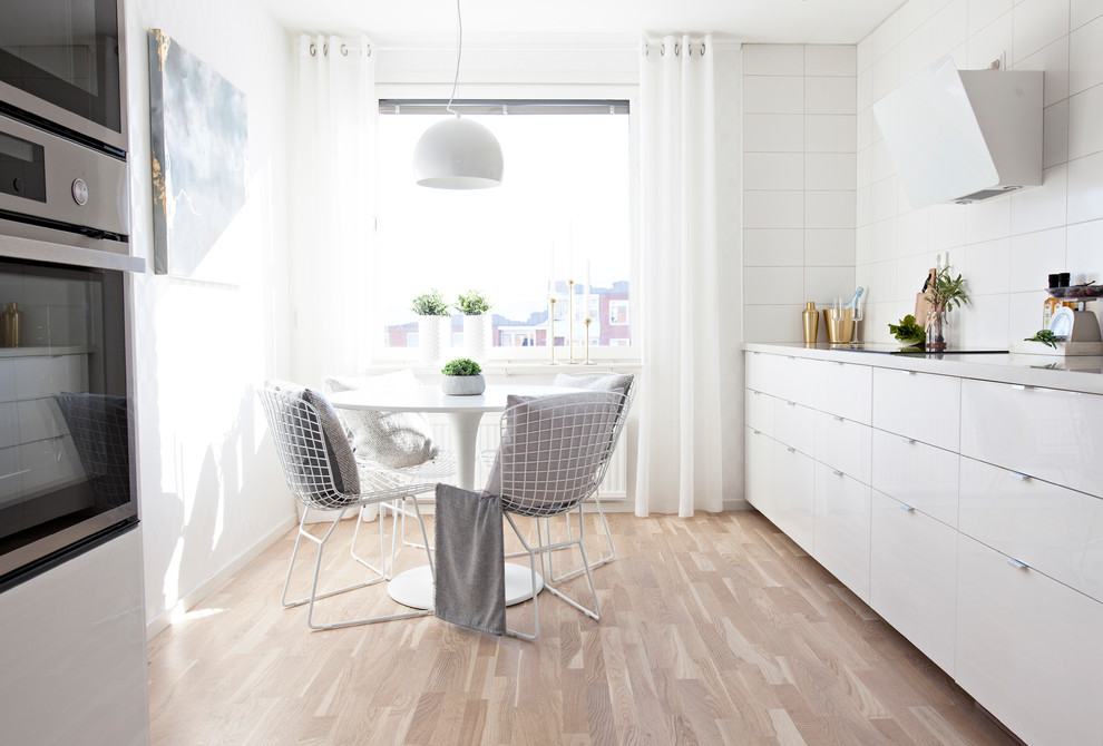 Danish galley light wood floor and beige floor eat-in kitchen photo in Other with flat-panel cabinets, white cabinets, white backsplash, no island and white countertops