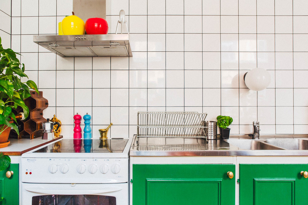 Small danish single-wall kitchen photo in Stockholm with a double-bowl sink, stainless steel countertops, white backsplash, porcelain backsplash and white appliances