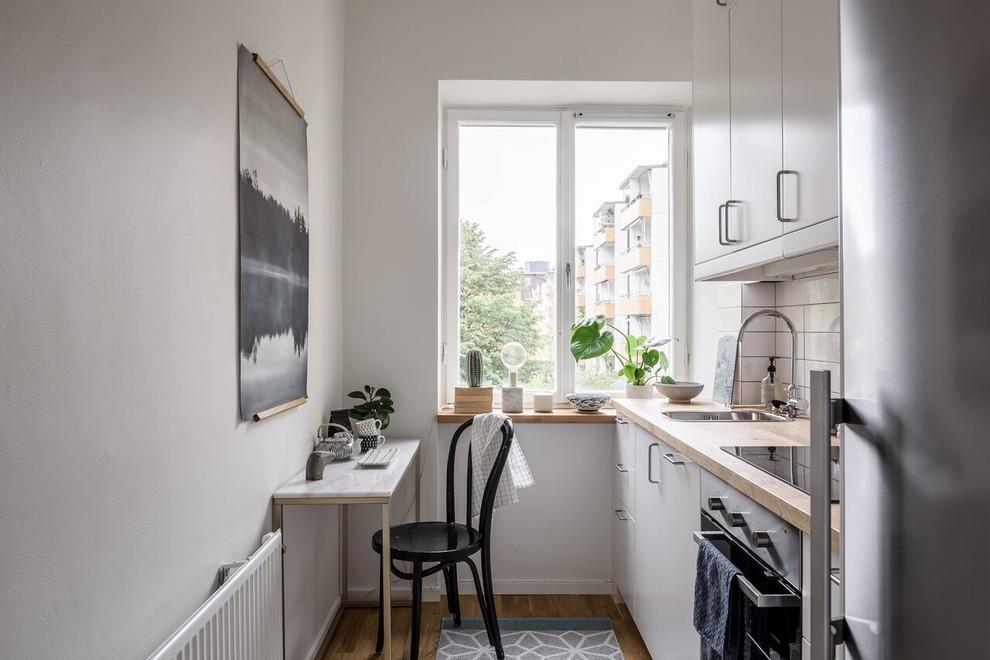Idéer för ett litet minimalistiskt linjärt kök och matrum, med släta luckor, vita skåp, träbänkskiva, vitt stänkskydd, mellanmörkt trägolv och brunt golv