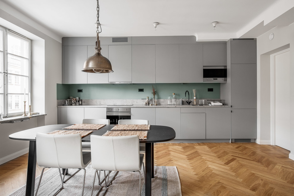 Example of a mid-sized danish single-wall medium tone wood floor eat-in kitchen design in Stockholm with flat-panel cabinets, gray cabinets, green backsplash, stainless steel appliances, marble countertops and no island