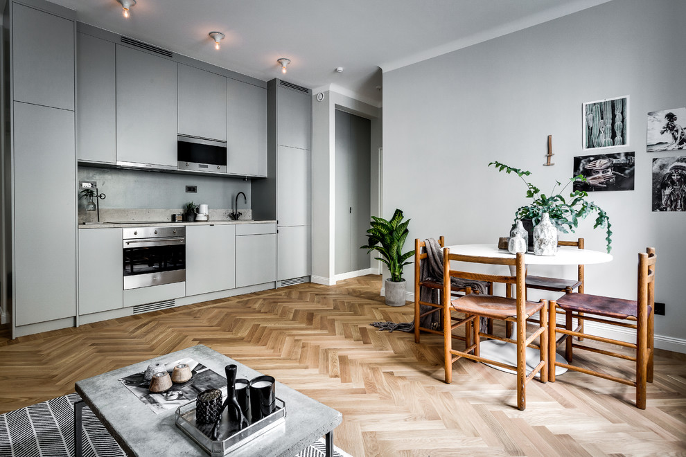 Design ideas for a large scandinavian single-wall open plan kitchen in Stockholm with flat-panel cabinets, grey cabinets, light hardwood flooring, no island and grey splashback.