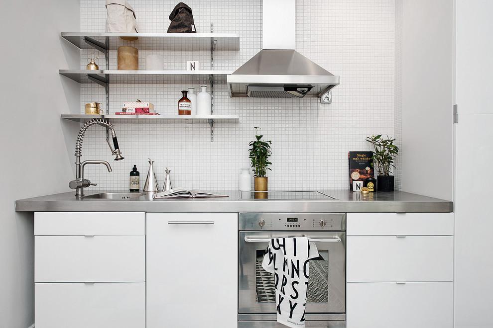 Inredning av ett skandinaviskt avskilt, litet linjärt kök, med en enkel diskho, släta luckor, vita skåp, bänkskiva i rostfritt stål och rostfria vitvaror