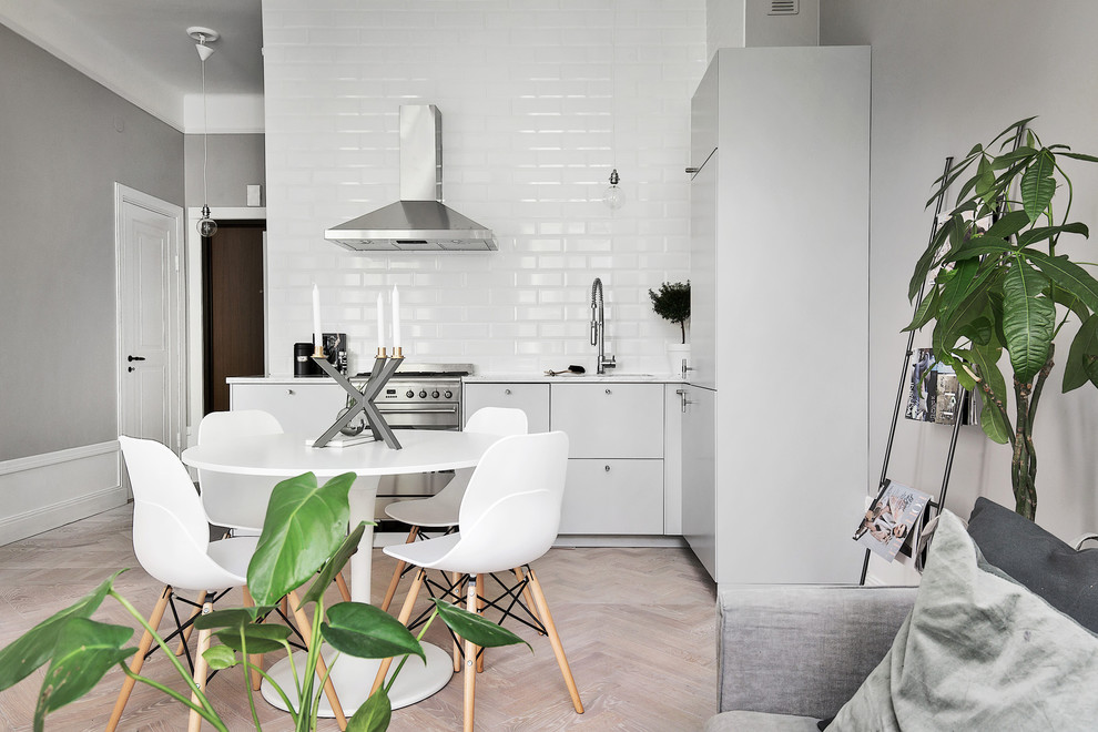 Mid-sized danish l-shaped light wood floor eat-in kitchen photo in Stockholm with an undermount sink, flat-panel cabinets, gray cabinets, white backsplash, subway tile backsplash, stainless steel appliances and no island