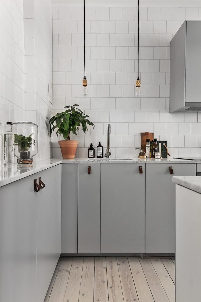 Exempel på ett nordiskt l-kök, med en enkel diskho, släta luckor, grå skåp, marmorbänkskiva och ljust trägolv