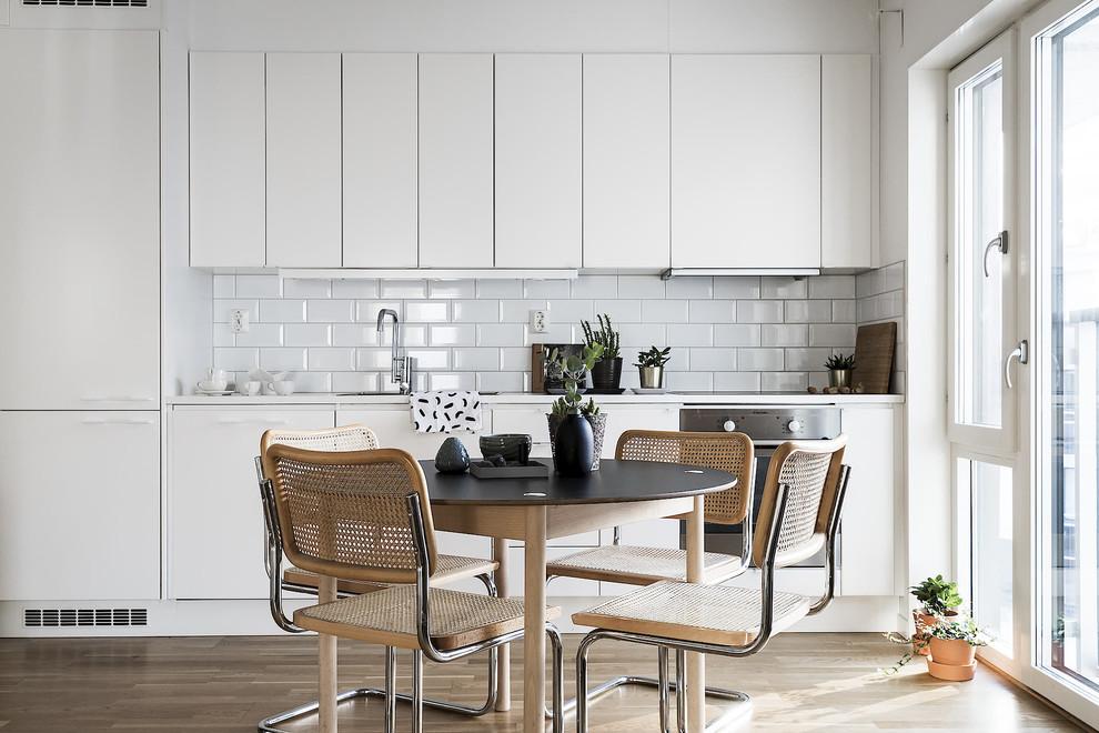 Inspiration för ett litet skandinaviskt vit linjärt vitt kök och matrum, med släta luckor, vita skåp, stänkskydd i tunnelbanekakel, vita vitvaror, beiget golv, vitt stänkskydd och ljust trägolv