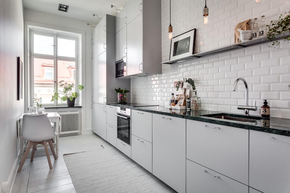 Idéer för att renovera ett stort minimalistiskt linjärt kök och matrum, med en undermonterad diskho, släta luckor, grå skåp, vitt stänkskydd, stänkskydd i tunnelbanekakel, svarta vitvaror och målat trägolv