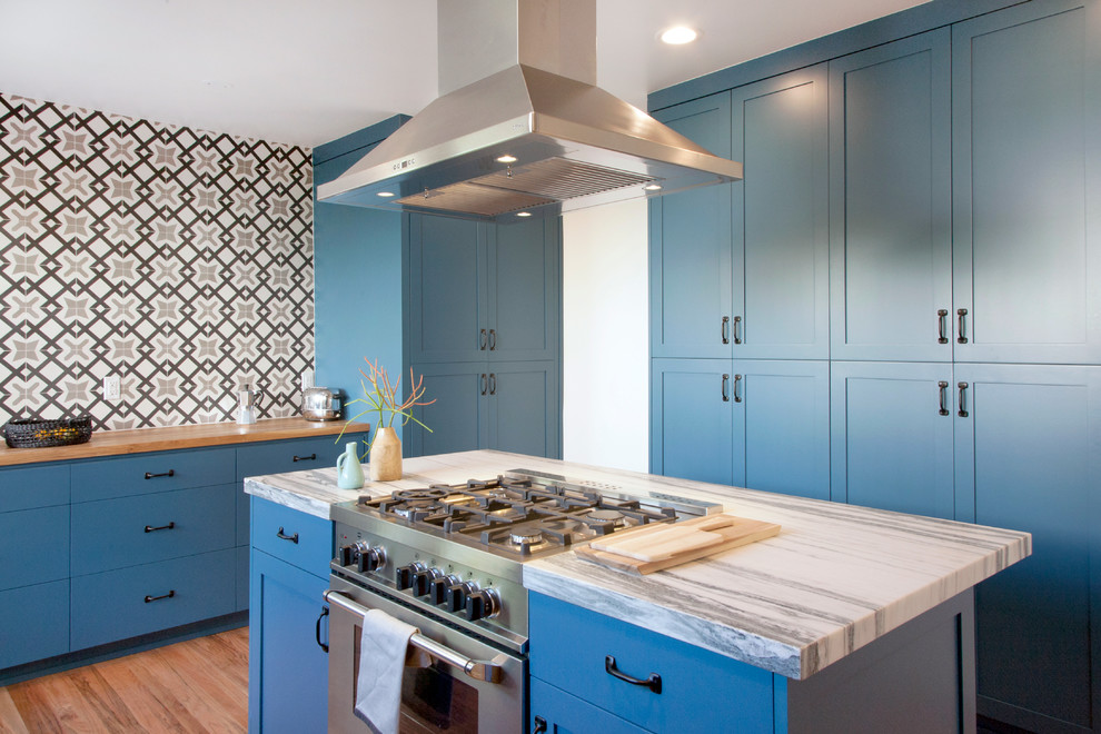 Inspiration for a mid-sized transitional single-wall light wood floor kitchen remodel in Stockholm with shaker cabinets, blue cabinets, multicolored backsplash, stainless steel appliances, an island and wood countertops