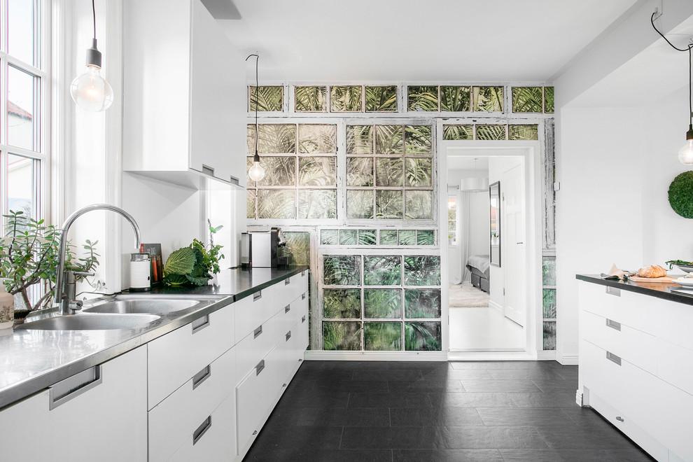 Idéer för att renovera ett stort nordiskt linjärt kök och matrum, med släta luckor, vita skåp, bänkskiva i rostfritt stål och vitt stänkskydd
