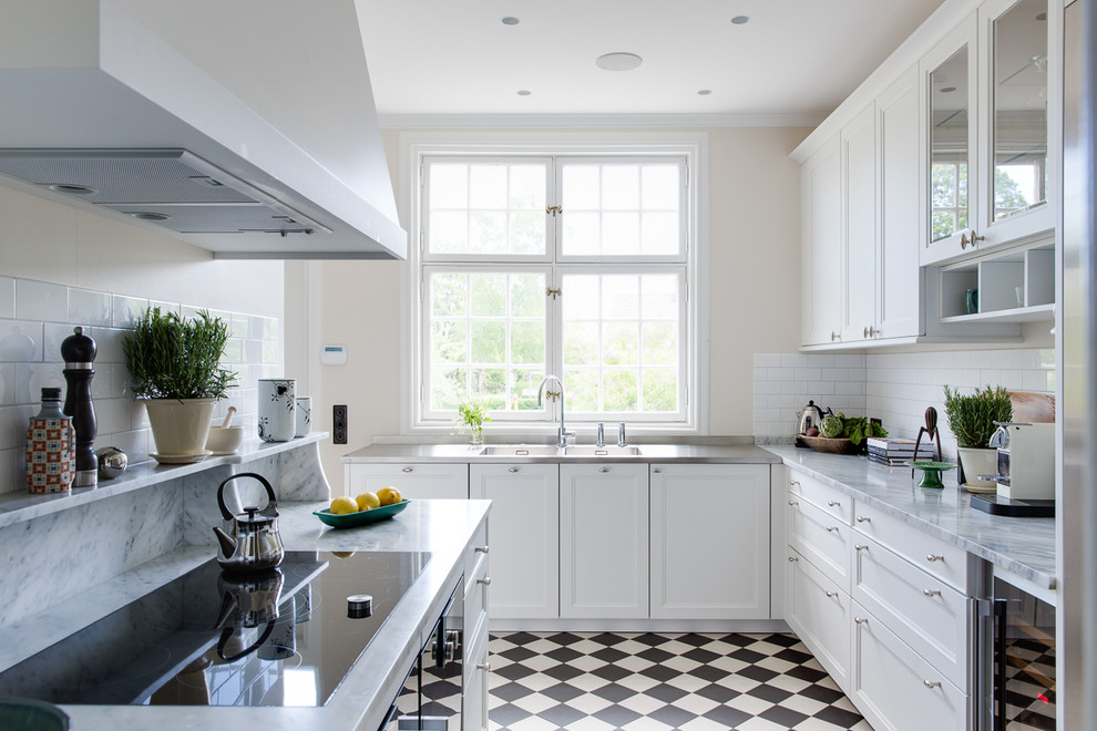 Mid-sized transitional l-shaped ceramic tile enclosed kitchen photo in Malmo with a double-bowl sink, recessed-panel cabinets, white cabinets, white backsplash, stainless steel appliances, no island and marble countertops