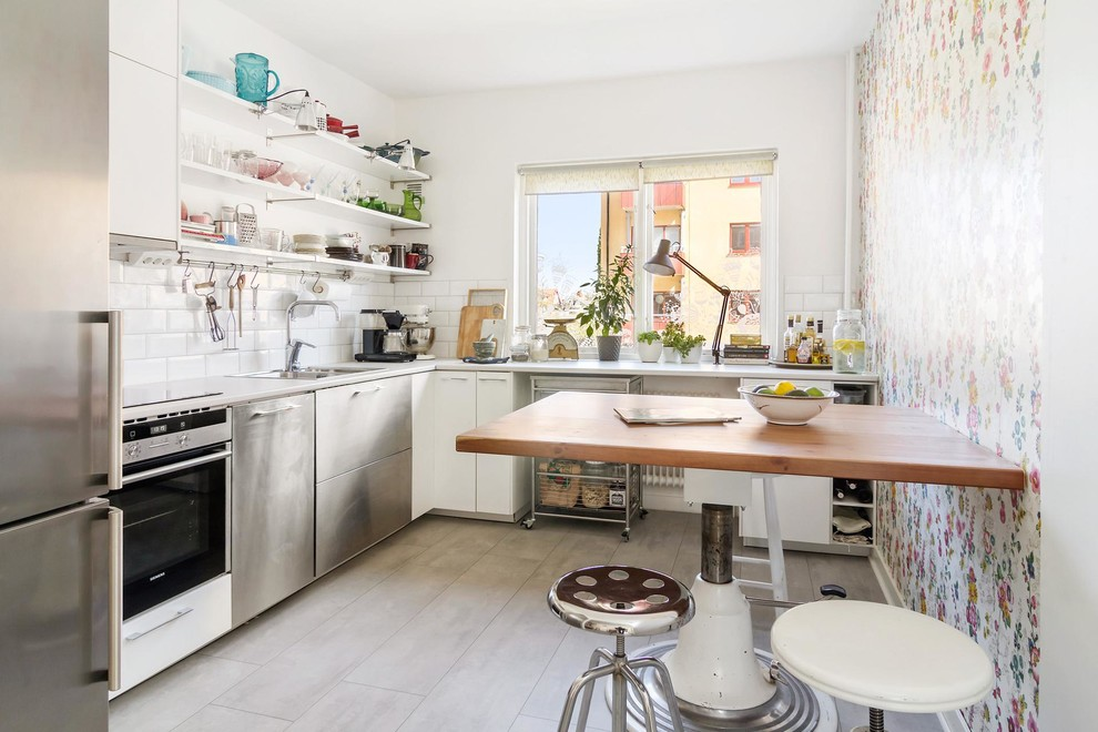Mid-sized danish l-shaped limestone floor enclosed kitchen photo in Orebro with a double-bowl sink, flat-panel cabinets, white cabinets, white backsplash, subway tile backsplash, stainless steel appliances, laminate countertops and no island