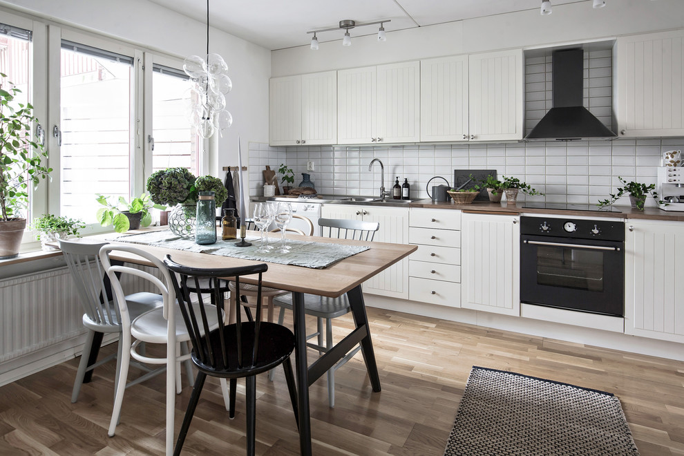 Inspiration for a mid-sized scandinavian single-wall medium tone wood floor and brown floor eat-in kitchen remodel in Gothenburg with a double-bowl sink, white cabinets, wood countertops, white backsplash, black appliances and no island