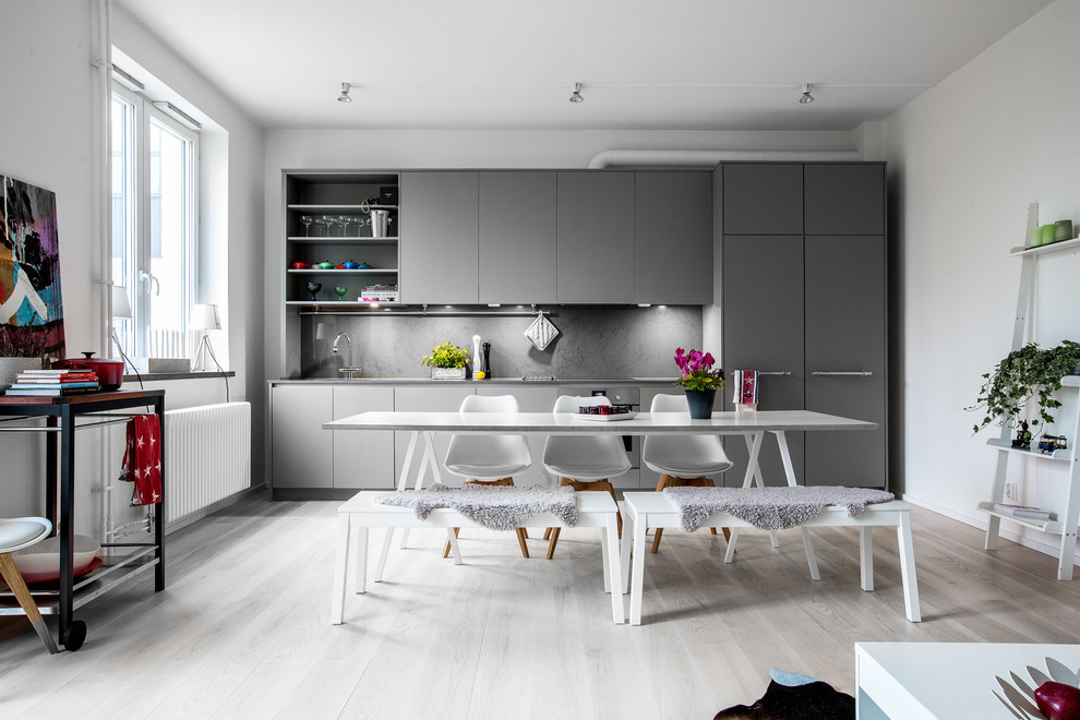 Example of a mid-sized danish single-wall light wood floor eat-in kitchen design in Stockholm with flat-panel cabinets, gray cabinets, gray backsplash and no island