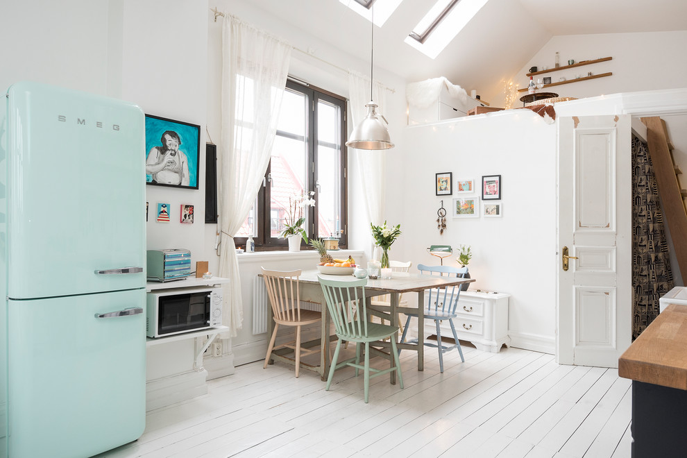 Example of a mid-sized danish painted wood floor open concept kitchen design in Malmo with a farmhouse sink, colored appliances, no island, raised-panel cabinets, white cabinets and wood countertops