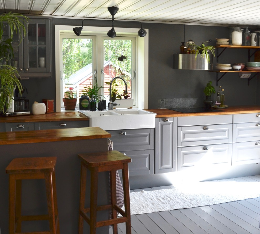 Inspiration for a mid-sized country single-wall painted wood floor and gray floor enclosed kitchen remodel in Stockholm with a farmhouse sink, beaded inset cabinets, gray cabinets, wood countertops, metallic backsplash, metal backsplash, stainless steel appliances, a peninsula and brown countertops