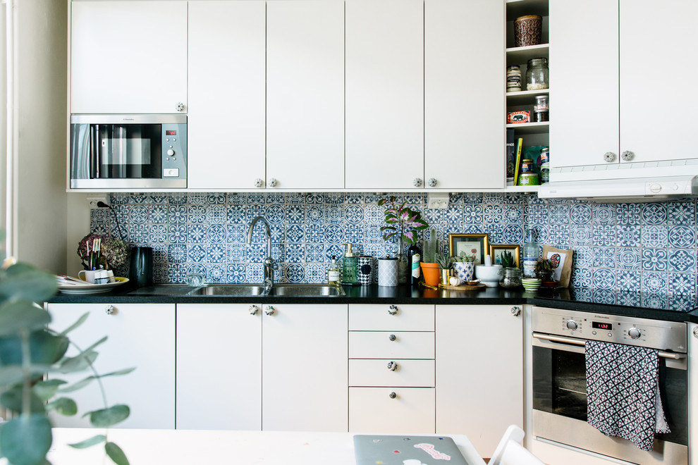 Mid-sized tuscan single-wall eat-in kitchen photo in Stockholm with a double-bowl sink, flat-panel cabinets, white cabinets, granite countertops, multicolored backsplash, porcelain backsplash, stainless steel appliances and no island