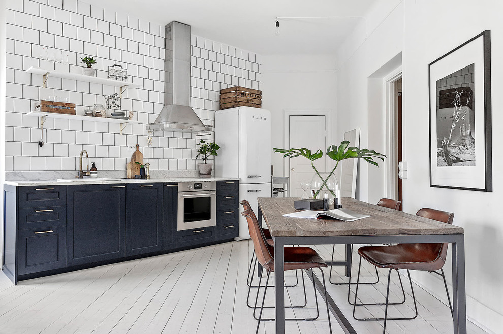 Eat-in kitchen - scandinavian single-wall painted wood floor and white floor eat-in kitchen idea in Stockholm with a drop-in sink, recessed-panel cabinets, blue cabinets, white backsplash and white appliances