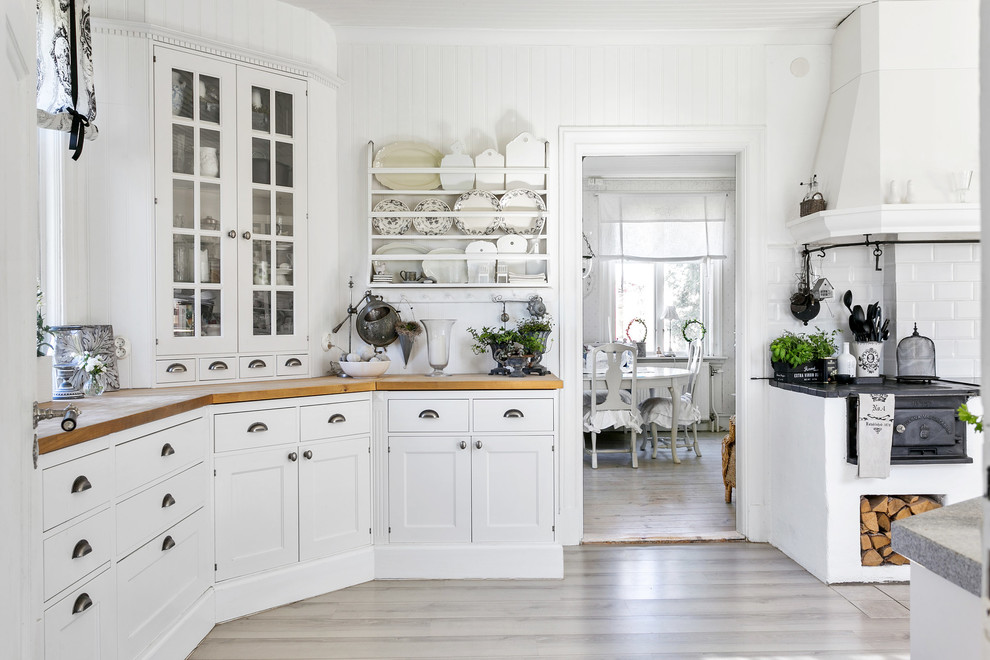 Inspiration for a shabby-chic style beige floor enclosed kitchen remodel in Other with glass-front cabinets, white cabinets, wood countertops, white backsplash and subway tile backsplash
