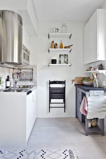 Ispirazione per una piccola cucina parallela nordica con lavello da incasso, ante lisce, ante bianche, paraspruzzi grigio, elettrodomestici in acciaio inossidabile, parquet chiaro e nessuna isola