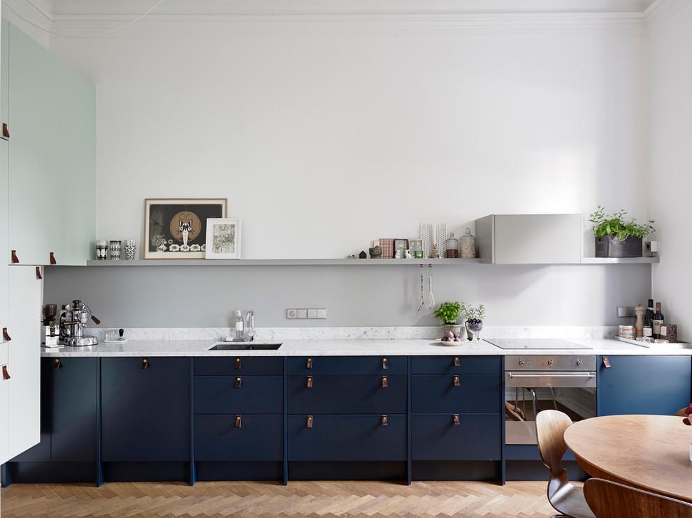 Inredning av ett minimalistiskt mellanstort linjärt kök och matrum, med en undermonterad diskho, blå skåp, grått stänkskydd, rostfria vitvaror, ljust trägolv, släta luckor och marmorbänkskiva