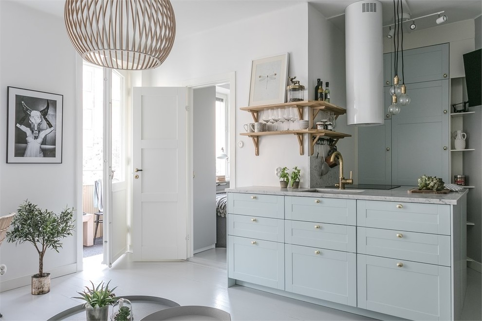 Example of a small danish painted wood floor and white floor kitchen design in Stockholm with a peninsula, marble countertops, a single-bowl sink and shaker cabinets