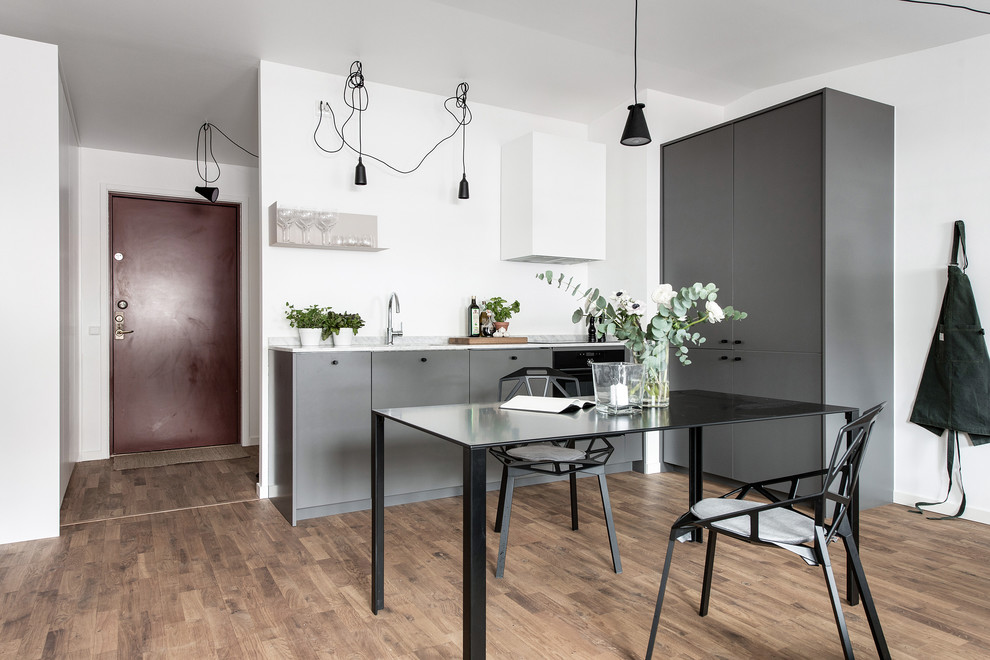 Small scandinavian l-shaped kitchen/diner in Gothenburg with medium hardwood flooring, brown floors, flat-panel cabinets, grey cabinets and no island.